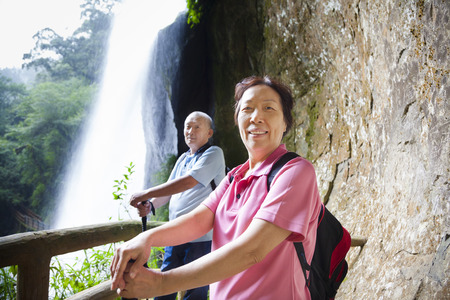asian senior couple hiking in the mountain with waterfall photo