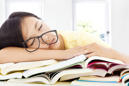 exam room: tired student girl with glasses sleeping on the books with room