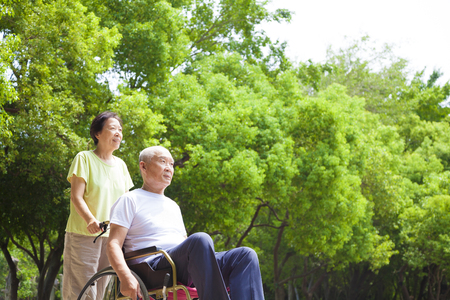 Asian senior man sitting on a wheelchair with his wife Stock Photo