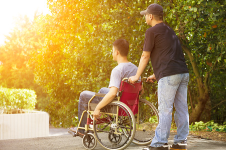 young man sitting on a wheelchair with his brother Foto de archivo