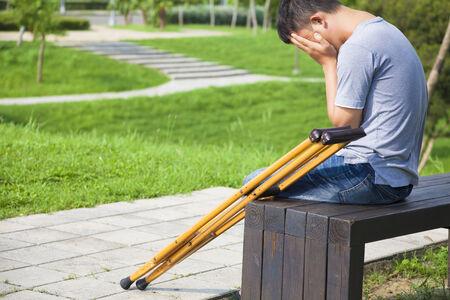 mirada triste: Hombre herido con muletas sentado en un banco Foto de archivo