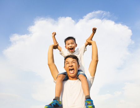 happy little boy sitting on father's shoulder photo