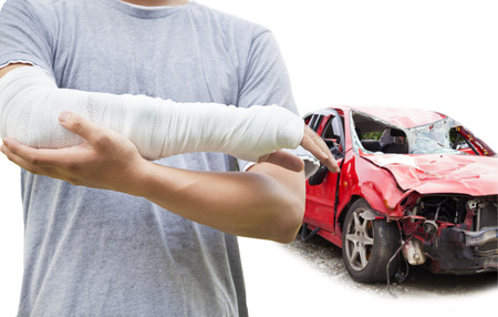 injure: closeup of bandaged arm with blue wrecked car Stock Photo