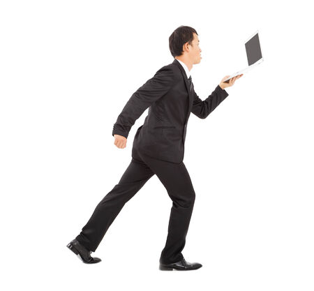 positive businessman running busily and holding a laptop photo