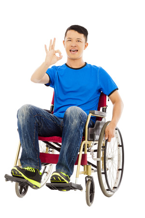 innate: happy young man sitting on a wheelchair and ok gesture