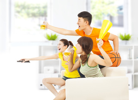 young people so excited to yelling and while watching tv photo