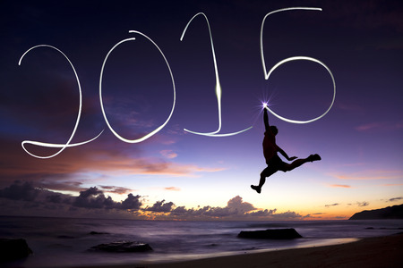 new year: happy new year 2015.young man jumping and drawing 2015 by flashlight Stock Photo