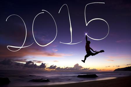 nouvel an: homme le saut et le dessin 2015 heureuse nouvelle ann�e de lampe de poche