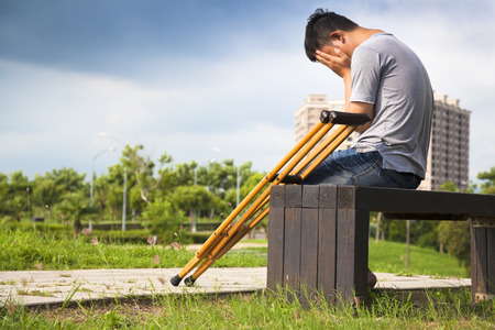 recuperating: Injured Man with crutches sitting on a bench