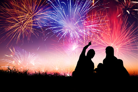 new Year: Famiglia felice seduta sul pavimento e guardare i fuochi d'artificio Archivio Fotografico