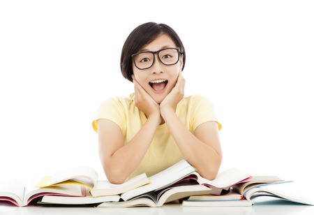 assignments: smiling young student girl thinking with book on the desk Stock Photo