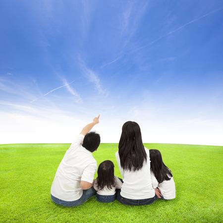 家族: 雲の背景を持つ草に幸せな家族