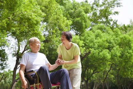 Asian senior muž sedící na invalidním vozíku s manželkou