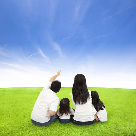 familias jovenes: familia feliz en un prado con el fondo de nubes
