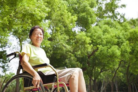 Asian senior woman sitting on a wheelchai in the park photo