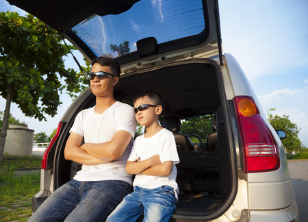 sit: little boy and father sitting on their car in the park