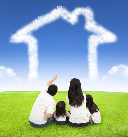 幸せな家族の青い空に雲の家で牧草地の上に座って