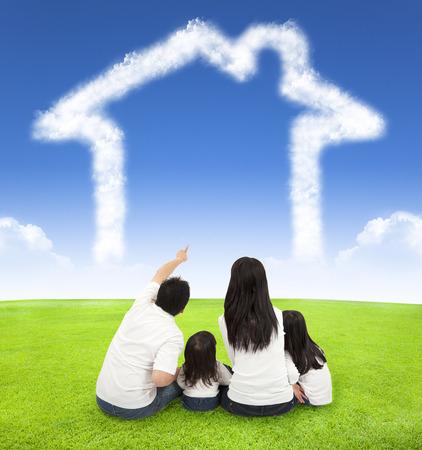 familias jovenes: familia feliz que se sienta en un prado con la casa de las nubes en el cielo azul