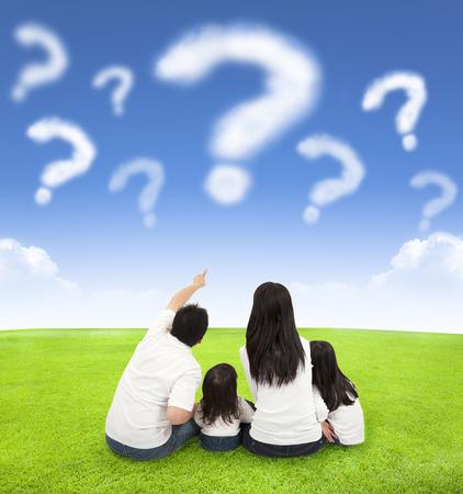 familia feliz que se sienta en un prado con la consulta de las nubes en el cielo azul de fondo