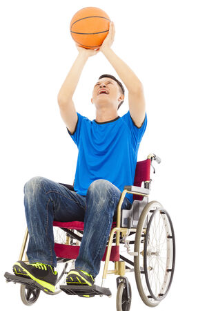 innate: young man sitting on a wheelchair and holding a basketball over white background