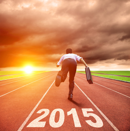 happy new year 2015. businessman running with sunrise background photo
