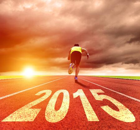 atletisch: Gelukkig Nieuwjaar 2015 jonge man lopen met zonsopgang achtergrond