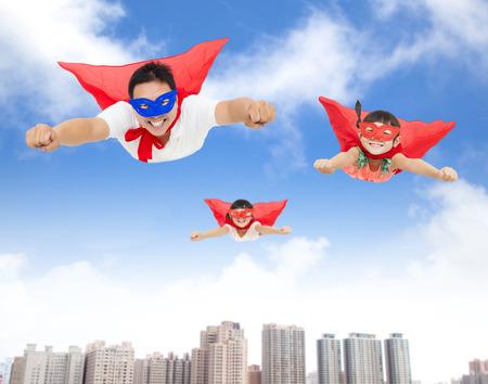 super human: superman y hijas volando en el cielo con edificios de fondo