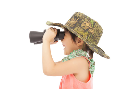 Little girl looking through binoculars. isolated on white backgrond photo