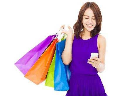 gelukkige jonge vrouw met boodschappentassen en mobiele telefoon op een witte achtergrond Stockfoto
