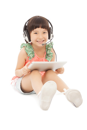 little student girl sitting and holding a tablet with earphone. isolated on white background photo