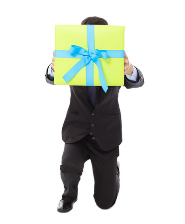 kneel down: Businessman holding a gift box and kneel down . isolated on white background