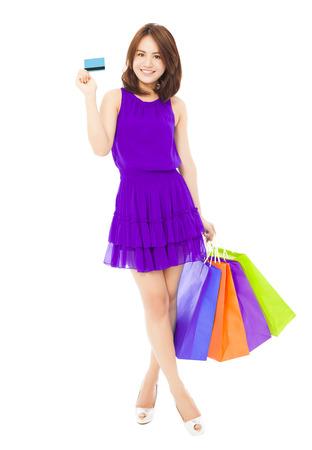 mujeres elegantes: hermosa mujer joven que sostiene una tarjeta y bolsas de compras. aislado en fondo blanco