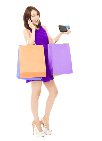 beautiful woman with shopping bags talking on phone over white background photo
