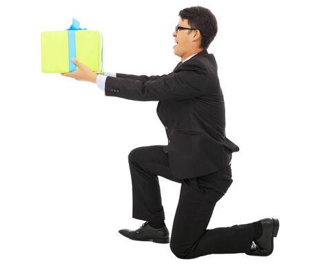 arrodillarse: joven hombre de negocios que sostiene una caja de regalo y arrodillarse. aislado en fondo blanco