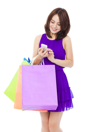 happy young woman holding shopping bags and mobile phone over white background photo