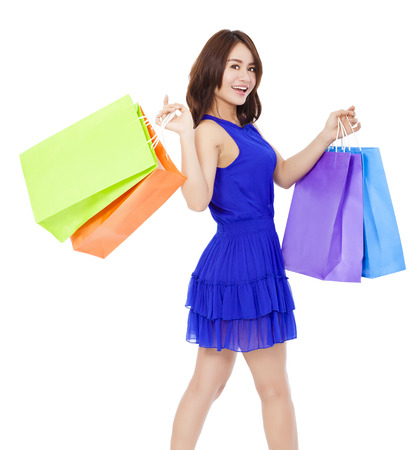 smiling young woman walking and  holding shopping bags over white background