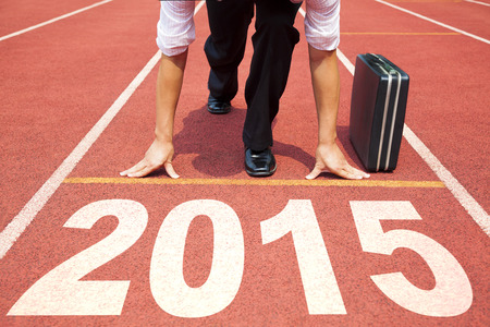 race: happy new year 2015. businessman preparing for running with briefcase