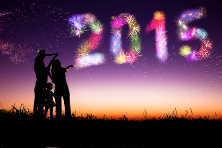 new year: happy new year 2015.family standing on the hill and watching the fireworks