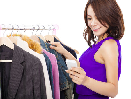 Happy asian Woman shopping clothes with a mobile phone over white background photo