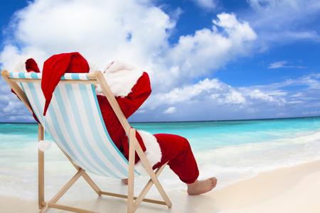 Vánoce Santa Claus odpočívá na pláži Reklamní fotografie