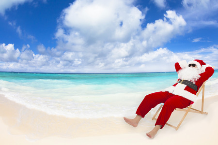 natal: Papai Noel sentado em cadeiras de praia com céu azul e nuvens. Conceito de férias de Natal. Banco de Imagens