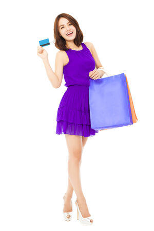 asian shopper: beautiful young woman holding a card and shopping bags. isolated on white