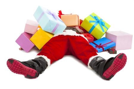 holiday celebration: santa claus too tired to lie on floor with many gift boxes over white background