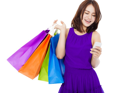 adult young: happy young woman holding shopping bags and mobile phone over white background Stock Photo