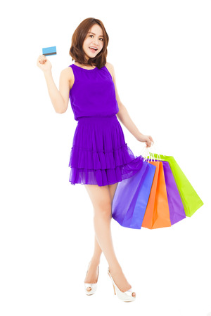 beautiful young woman holding a card and shopping bags. isolated on white  photo
