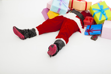 fun: santa claus too tired to lie on floor with many gift boxes over white