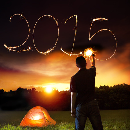 happy new year 2015. young man drawing 2015 by sparkling stick. camping on the mountain