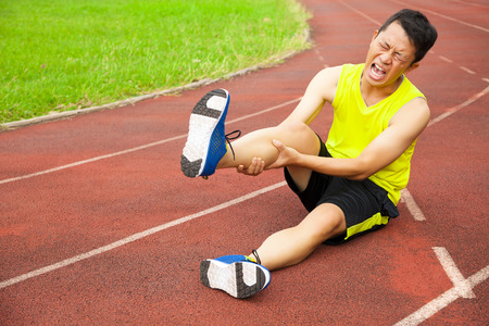 young male runner suffering from leg cramp on the track in the stadium Standard-Bild