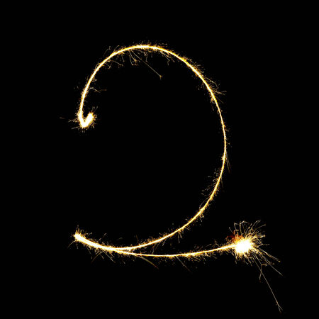 number two: burning sparkler stick and writing sparkling text . number two  isolated on black  Stock Photo