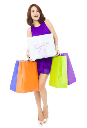 fancy box: happy young woman holding shopping bag and a gift boxes over white